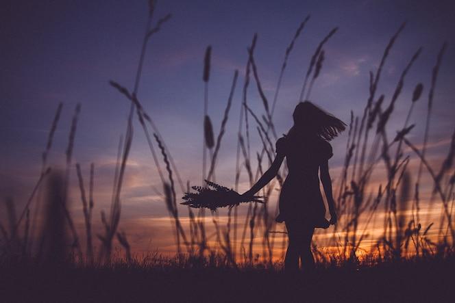 Sylwetka dziewczyny trzymającej bukiet kwiatów na łące na tle zachodu słońca