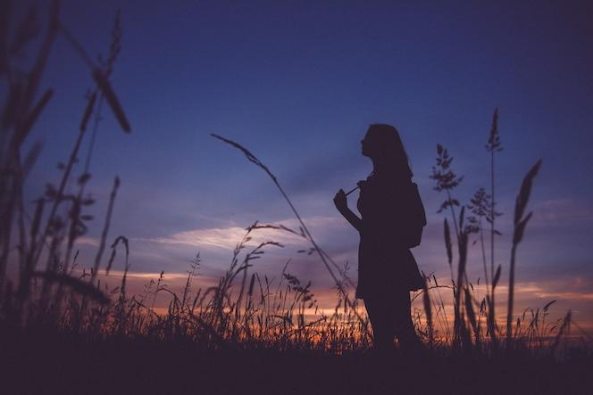 Sylwetka dziewczyny z plecakiem na łące na tle zachodu słońca