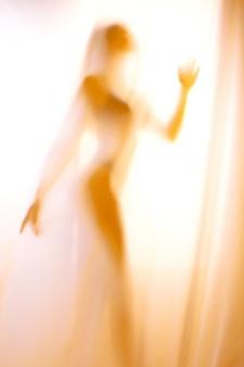 Sylwetka dziewczyny za zasłoną. abstrakcyjny i zamazany obraz dziewczyny