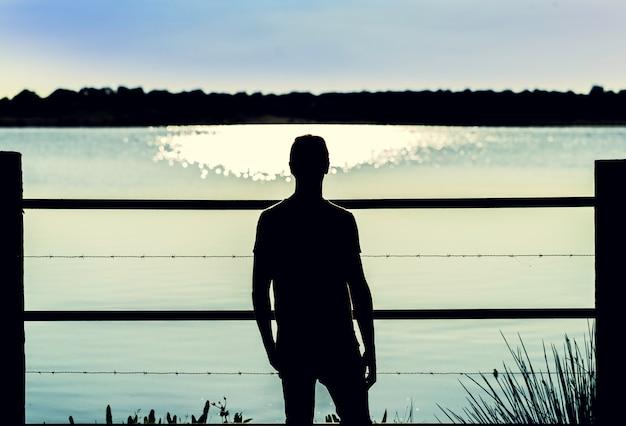 Sylwetka faceta pozycja w drutu kolczastego ogrodzeniu patrzeje wodę bagno