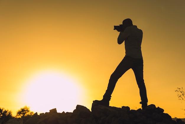 Sylwetka fotograf bierze fotografie przy zmierzchem z kopii przestrzenią.