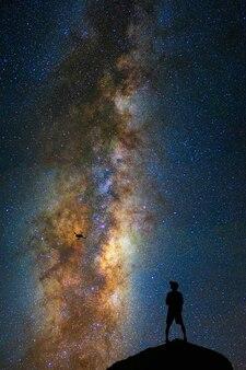 Sylwetka fotograf z trutniem nad milky sposobem na ciemnym niebie