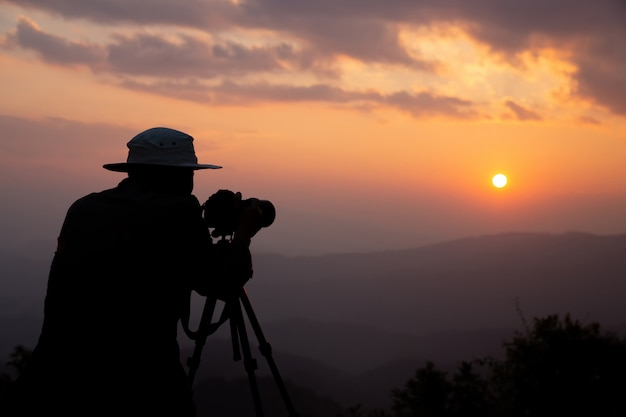 Sylwetka fotografa, który fotografuje zachód słońca w górach