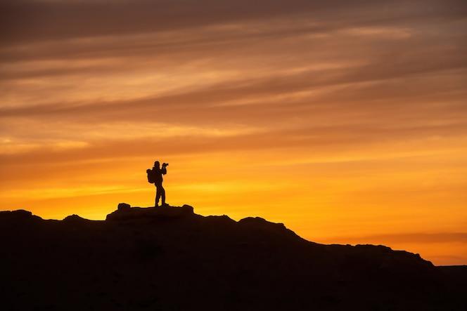 Sylwetka fotografa na widoku z góry podczas zachodu słońca, fotograf robi zdjęcie na szczycie góry o zachodzie słońca
