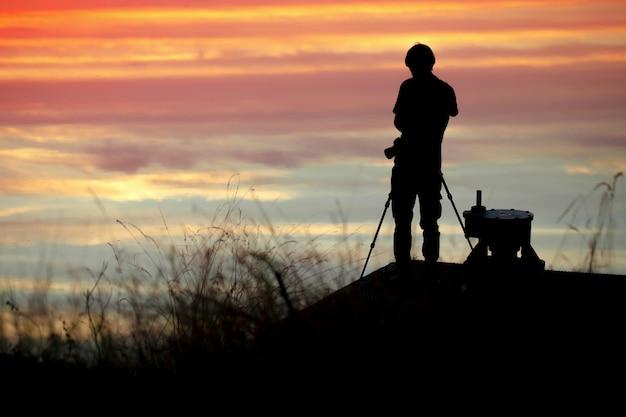 Sylwetka fotografa w zachodzie słońca z kolorowe dramatyczne niebo