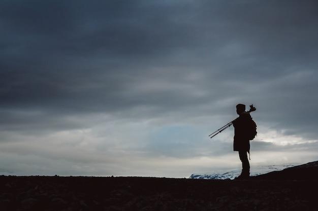 Sylwetka fotografa ze statywem stoi na brzegu na tle zachmurzonego nieba