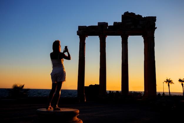 Sylwetka fotografuje na telefonie dziewczyna świątynia apollo przy zmierzchem