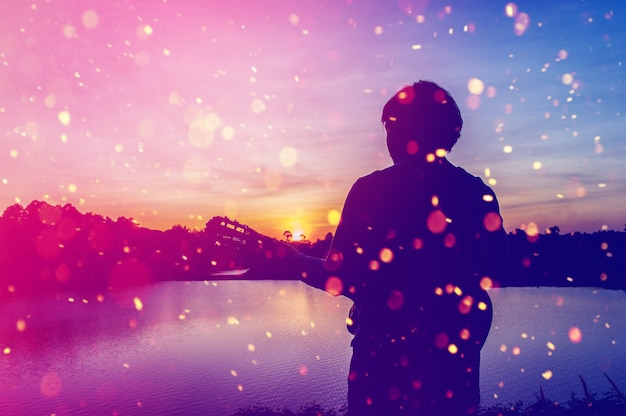 Sylwetka gitarzysta w cieniach przy zmierzchu światłem, sylwetki pojęcie.