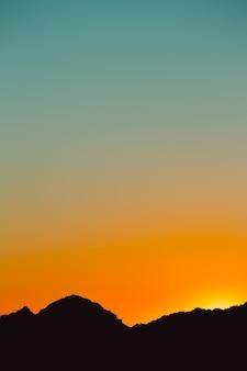 Sylwetka góry w kolorze czarnym z gradientem nieba zachodzącego słońca w kolorze pomarańczowym i niebieskim