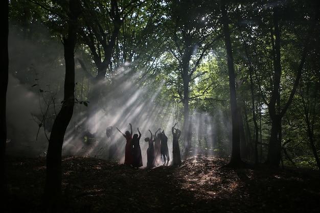 Sylwetka grupa kobiet w ciemnym lesie z dymem