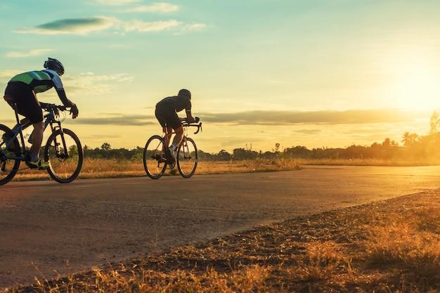 Sylwetka grupa mężczyzna jedzie bicykl przy zmierzchem.