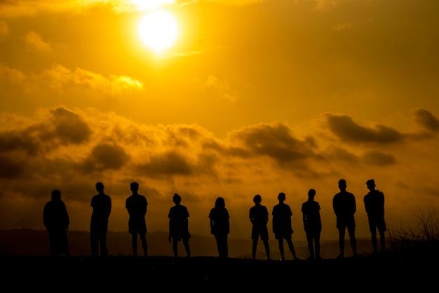 Sylwetka grupy ludzi świętuje sukces na szczycie wzgórza.