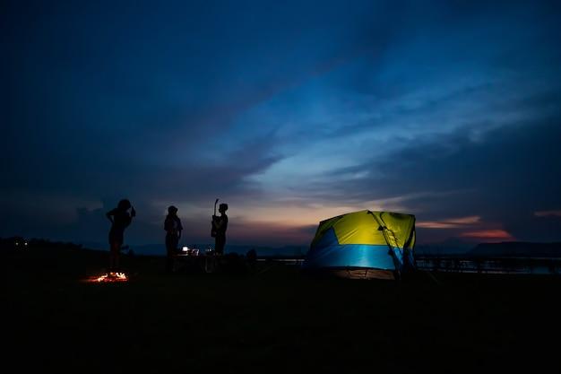 Sylwetka grupy turystów azjatyckich przyjaciół picia i gry na gitarze wraz ze szczęściem w lecie, mając kemping w pobliżu jeziora