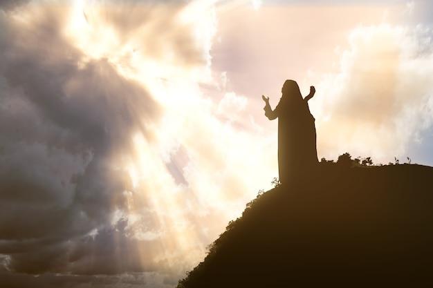 Sylwetka jezusa chrystusa modlącego się do boga z dramatycznym niebem
