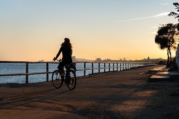 Sylwetka kędzierzawa kobieta jedzie bicykl przy zmierzchem na deptak drodze