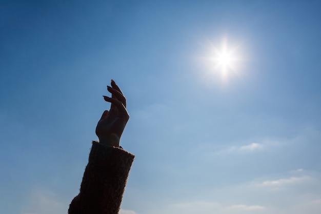 Sylwetka kobiecej dłoni na tle błękitnego nieba i jasnego słońca