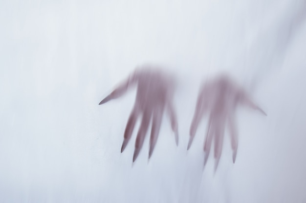 Sylwetka kobiecej postaci seksualnej za mglistym szkłem. koncepcja ducha poltergeist z innego świata. przerażające ręce śmierci przez tkaninę.
