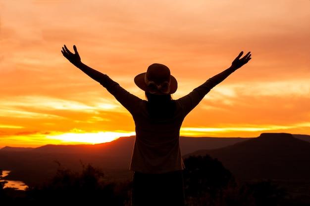 Sylwetka kobieta stoi na szczycie góry w zachód słońca, wolności szczęśliwą kobietą, podziwiając zachód słońca natura