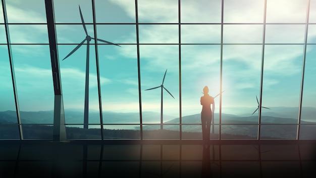 Sylwetka kobiety biznesu stoi przed oknem biura z widokiem na farmy wiatrowe
