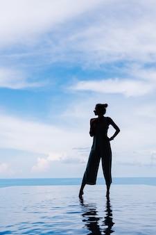 Sylwetka kobiety chodzącej po tafli wody basenu bez krawędzi drogiej luksusowej willi na górze z widokiem na morze