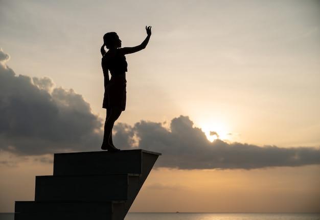 Sylwetka kobiety chodzenia po schodach w zachód słońca.