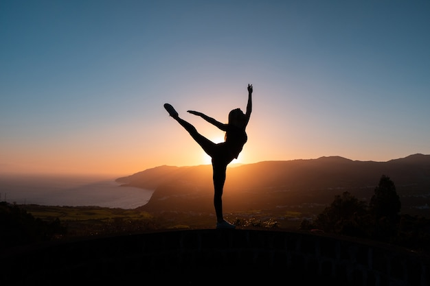 Sylwetka kobiety cieszącej się wolnością, czując się szczęśliwy o zachodzie słońca z górami i morzem