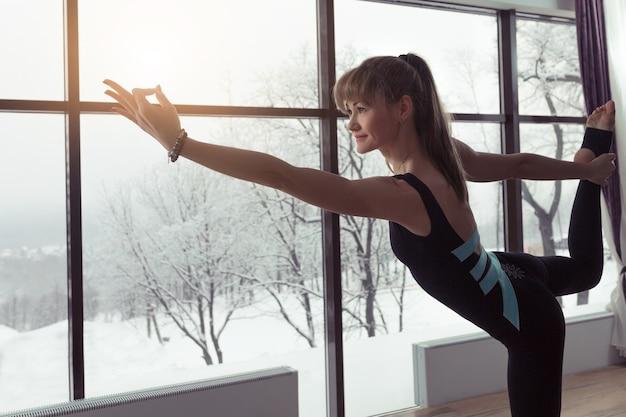 Sylwetka kobiety ćwiczącej jogę na tle okien z pięknym zimowym krajobrazem