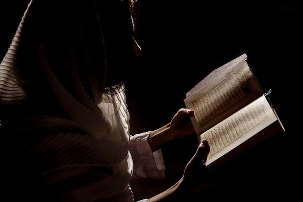 Sylwetka kobiety czytanie w koranie