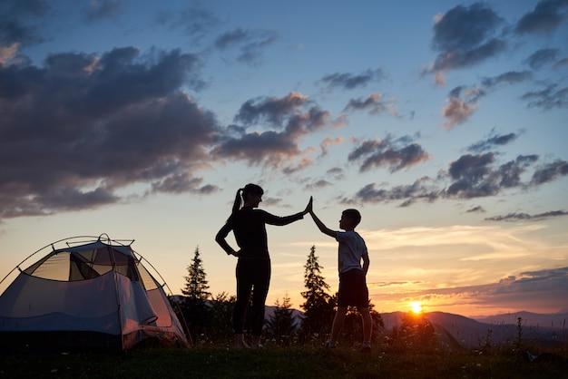 Sylwetka kobiety i dziecka daje sobie piątkę w pobliżu kempingu o świcie na szczycie góry. piękny krajobraz jodły i słońca wznoszącego się nad górami i wzgórzami