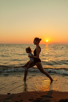 Sylwetka kobiety i dziewczyny uprawiania równowagi jogi