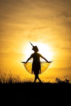Sylwetka kobiety manohra tańczą z zachodem słońca w południowej tajlandii.