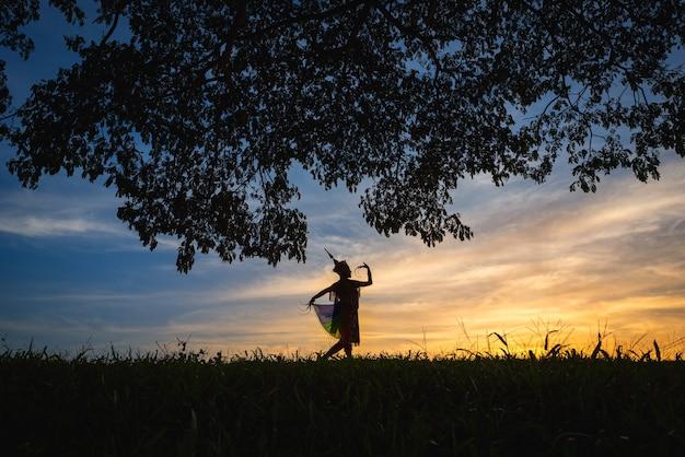 Sylwetka kobiety manohra taniec i drzewo z zachodem słońca w południowej tajlandii.