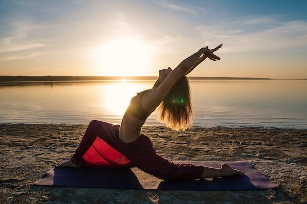 Sylwetka kobiety na plaży o zachodzie słońca robi asany jogi. poranny trening rozgrzewkowy z naturalnym rozciąganiem