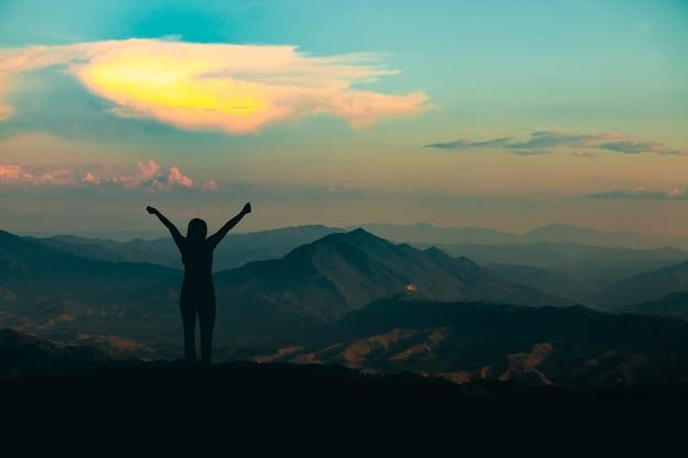 Sylwetka kobiety na szczycie góry na tle nieba i światła słonecznego, biznes, sukces, przywództwo, osiągnięcia i koncepcja ludzi