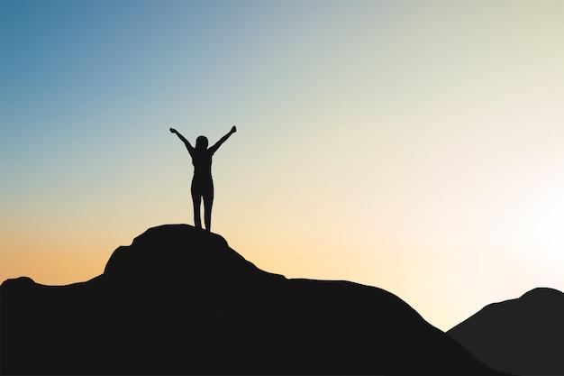 Sylwetka kobiety na szczycie góry nad niebo i słońce jasnym tle