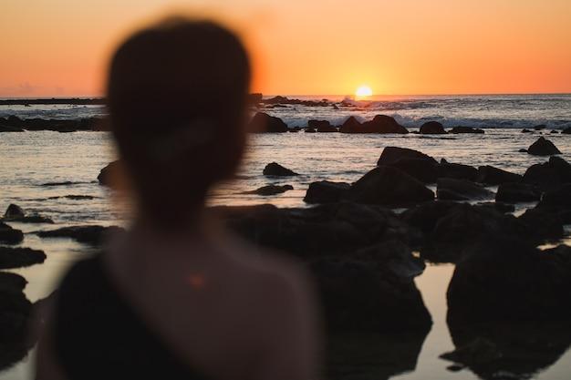 Sylwetka kobiety na tle oceanu indyjskiego i czarne skały o zachodzie słońca