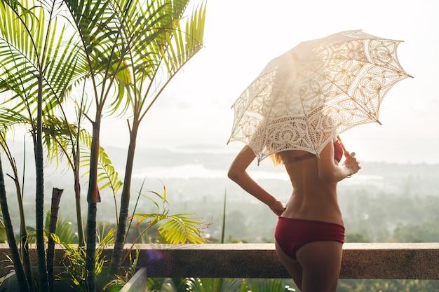 Sylwetka kobiety o pięknym, szczupłym ciele, ubrana w czerwony strój kąpielowy bikini, trzymająca koronkowy parasol słoneczny w słonecznym tropikalnym kurorcie willi na wakacjach w podróży na bali, chuda sylwetka, akcesoria w stylu letnim