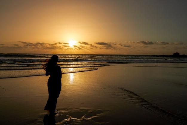 Sylwetka kobiety oglądając zachód słońca na plaży.
