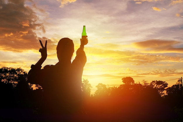 Sylwetka kobiety podniosła ręce, trzymając zieloną butelkę piwa na zachodzie słońca,