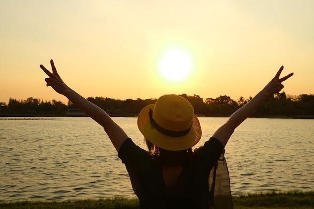 Sylwetka kobiety podnoszącej ręce szczęśliwa z pięknego wschodu słońca