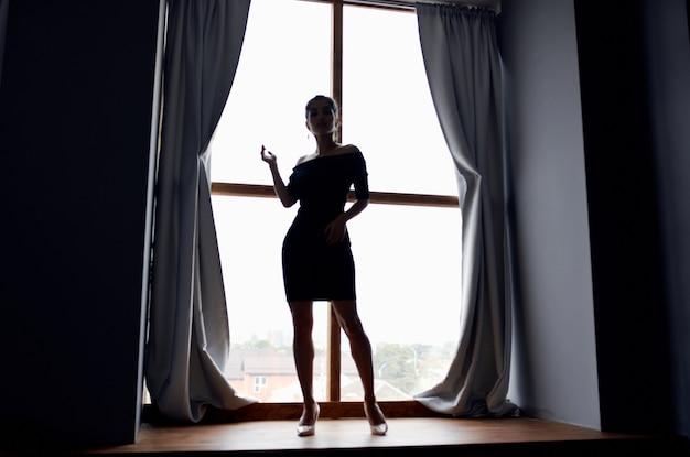 Sylwetka kobiety pozującej w pobliżu modelu okna