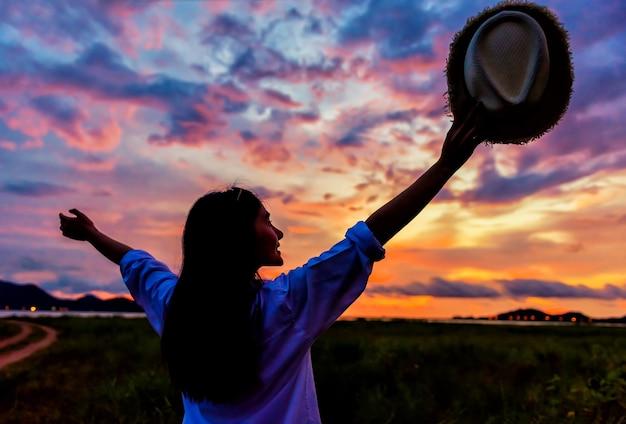 Sylwetka kobiety rekreacja i wolność na tle zachodu słońca. młody turysta w tajlandii na letnie wakacje.