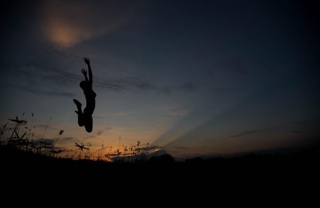 Sylwetka kobiety skaczącej o zachodzie słońca
