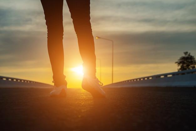 Sylwetka kobiety spaceru na ulicy o zachodzie słońca.
