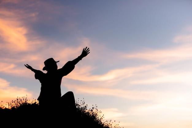 Sylwetka kobiety świętuje sukces na szczycie wzgórza w zachodzie słońca