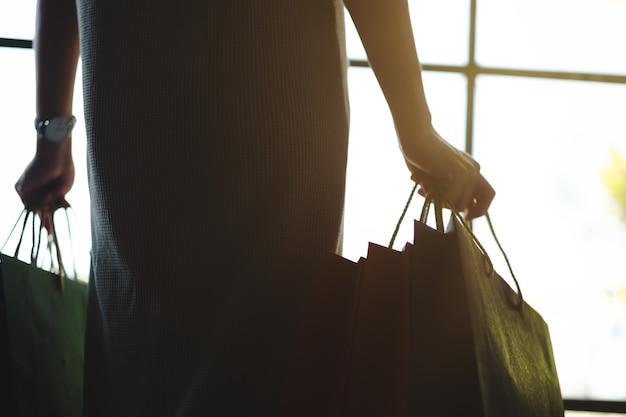 Sylwetka kobiety trzymającej kolorowe torby na zakupy