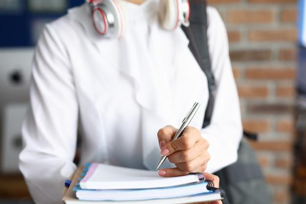 Sylwetka kobiety w białej koszuli ze słuchawkami na szyi trzyma zeszyty i długopis