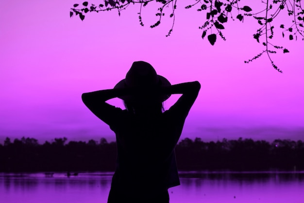 Sylwetka kobiety w kapeluszu z pięknym fioletowym różowym brzegiem jeziora w tle