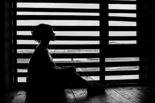 Sylwetka kobiety w oknie domu zimą, delikatne i zamyślone posiedzenie na podłodze