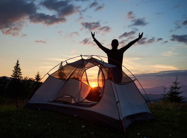 Sylwetka kobiety w pobliżu namiotu o zachodzie słońca